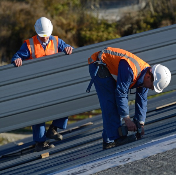 Commercial roofers setting installing metal plates