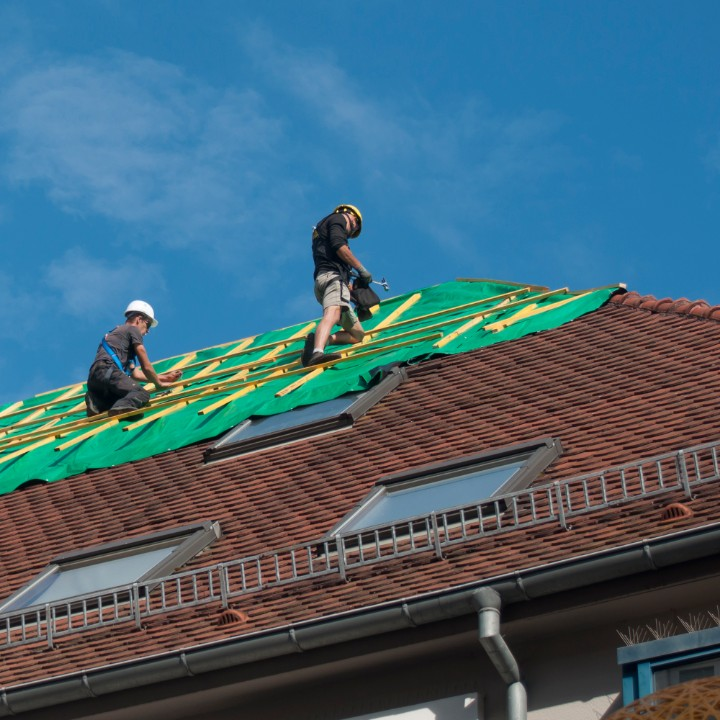 roofers repairing a commercial roof with skylights